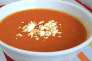 Butternut Squash and Roasted Red Pepper Soup in a White Bowl on the Table Closeup