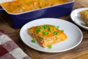 Creamy Chicken Enchilada Casserole - Focus on the Plate with a Piece of the Dish Near the Blue Tray