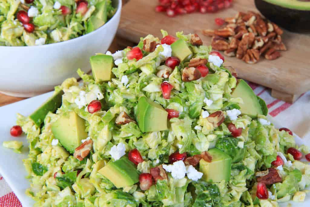 Shredded Brussels Sprout Pomegranate Salad with Honey Mustard Dressing - with Nuts and Pomegranate Seeds in the Background