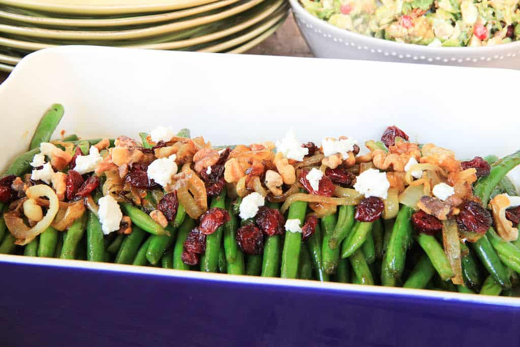 Brown Sugar Glazed Green Beans with Caramelized Onions, Cranberries, Walnuts and Goat Cheese with Plates in the Background