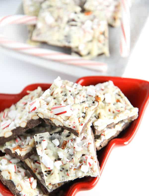 Peppermint Pretzel Bark ready and served in a red bowl in the shape of a Christmas tree.