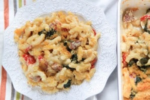 Salami Spinach and Roasted Red Pepper Mac and Cheese - Served in a White Plate Next to the Blue Casserole