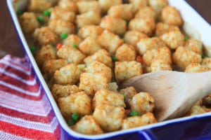 Tater Tot Hot Dish Closeup on the Tray with a Wooden Spoon