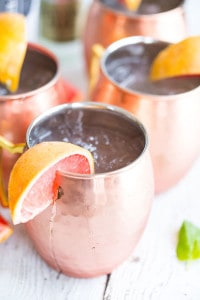 Grapefruit Moscow Mules - with Grapefruit Juice Dripping Over the Jar on a White Table