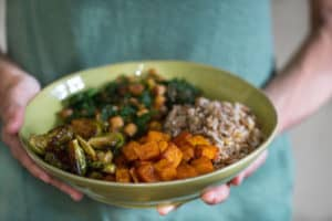 Autumn Nourish Bowls with Maple Almond Dressing - Hands Holding the Healthy and Flavordul Dish