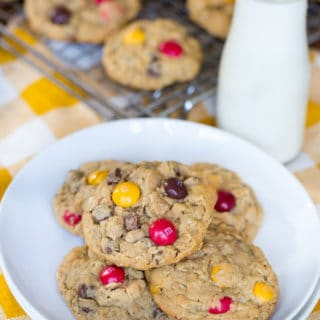 Peanut Butter M&M Oatmeal Cookies on top of two white plates with a bottle of milk blurred in the background