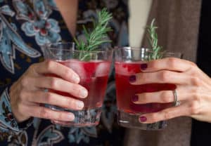 Cranberry Sauce Vodka Smash Cheering with Two Glasses Held in Hands