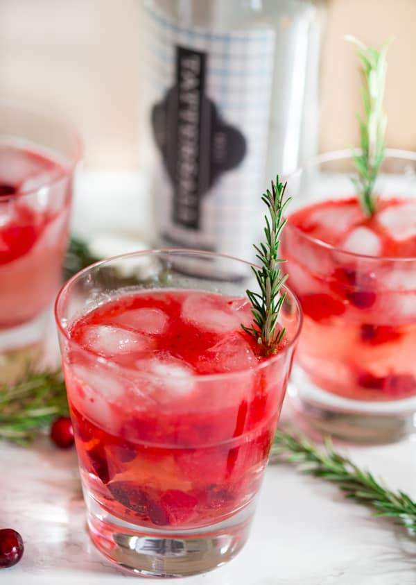 Cranberry Sauce Vodka Smash with Rosemary Decoration and Cranberry Berries around the Glasses
