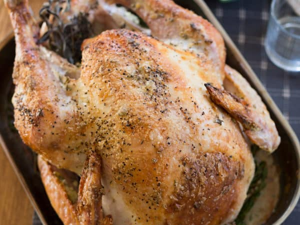 Garlic and Herb Mayonnaise Roasted Turkey on a Table with Stuffing Next to It