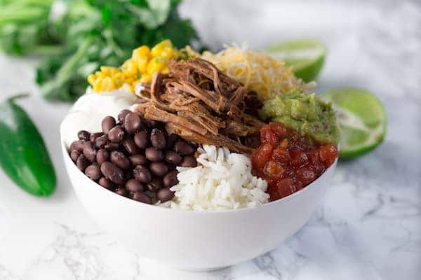 Slow Cooker Barbacoa Beef Burrito Bowls - Served in a White Bowl with Lime at the Side