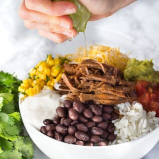 Slow Cooker Barbacoa Beef Burrito Bowls - Squeezing Lime Juice on Top with Parsley at the Side of the White Bowl