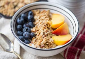 Coconut Maple Pecan Granola Beauty Shot with a Full Bowl of Granola, Berries and Peaches, and a Spoon Right Next to It