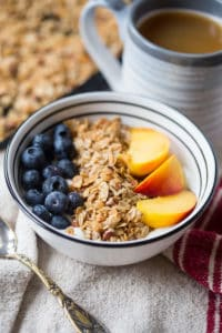 Coconut Maple Pecan Granola with a Full Cup of Drink Blurred in the Background