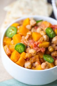 Butternut Squash Chana Masala in a Bowl on the Table with the Rest of the Meal Blurred in the Background