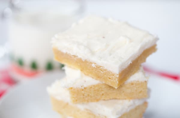A stack of three Eggnog Sugar Cookie Bars in the center of the frame looking delicious