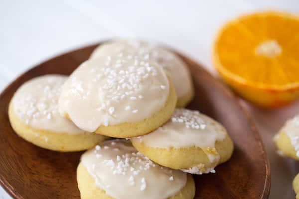 Orange Almond Ricotta Cookies piled up with an orange half blurred in the background