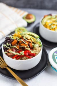 Vegetarian Quinoa Burrito Bowls with Avocado Cream Sauce - on the Table with a Piece of Fabrics in the Background