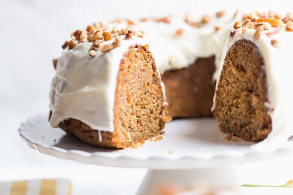 Carrot Bundt Cake with Cream Cheese Frosting Served on a White Plate. Someone Already Started It