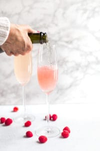 Raspberry Mimosas - Pouring a Bit More of the Drink into the Two Glasses
