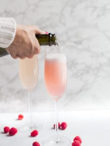 Raspberry Mimosas - Pouring into the Glass with Raspberries Around
