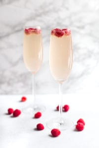 Raspberry Mimosas - Side Shot of Two Glasses with Raspberries Inside and Around on the Table
