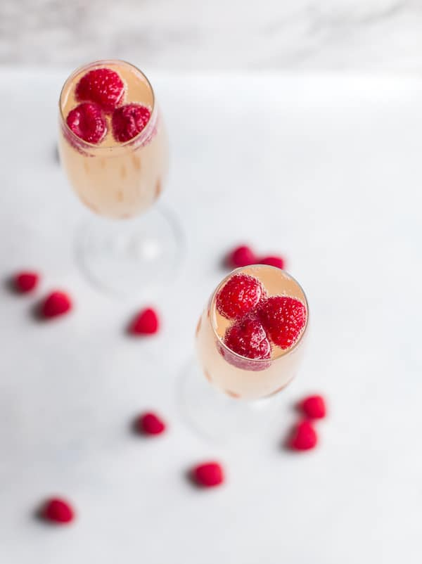 Raspberry Mimosas - Overhead Shot of Two Glasses with Raspberries Inside