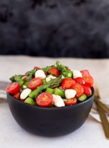 Asparagus Caprese Salad Beautiful Shot with a Dark Background and a Light Table