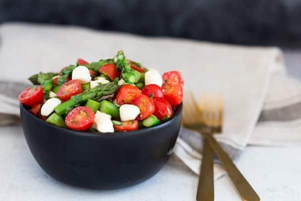 Asparagus Caprese Salad with Two Forks on the Right Side of the Bowl on the Table