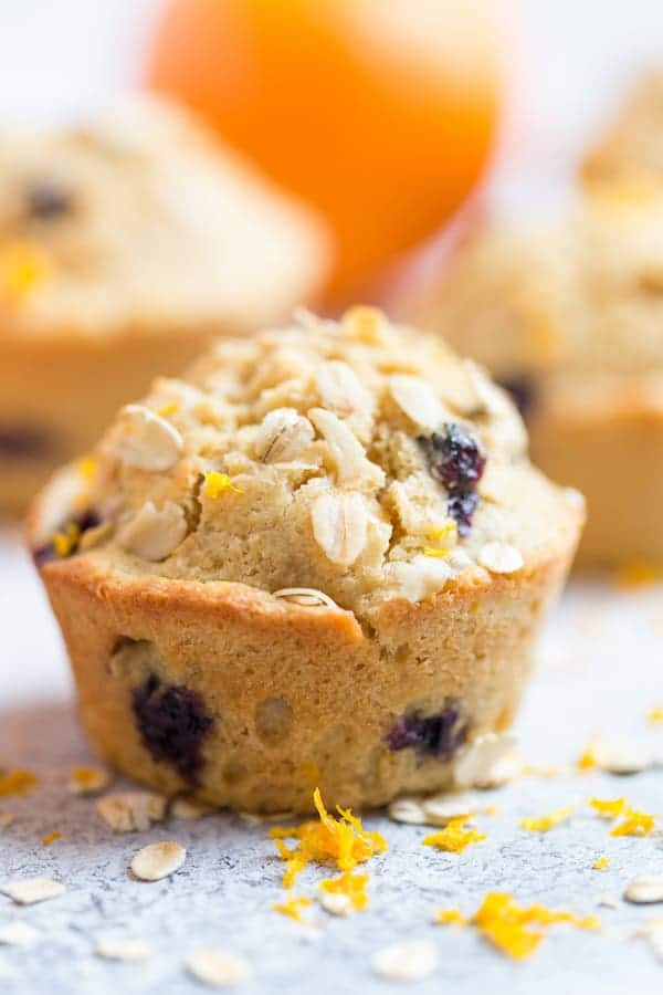 Blueberry Orange Oat Muffins Closeup on the Tasty Muffin with Other Muffins and Orange Blurred in the Back