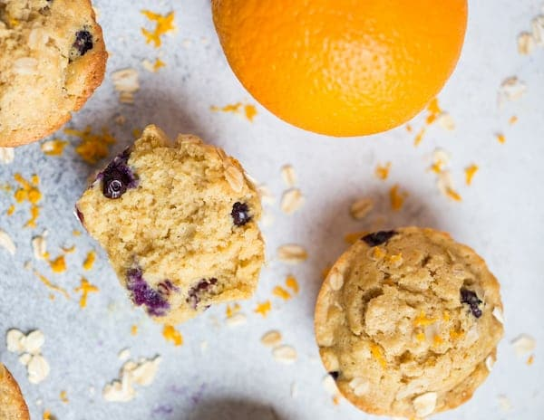Blueberry Orange Oat Muffins Overhead on the Muffins and a Big Orange