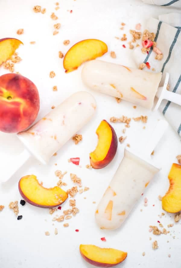 Peach Cheesecake Popsicles served with peach pieces around