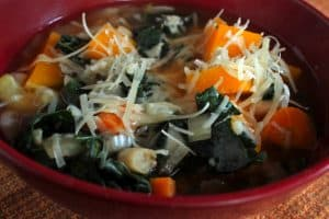 Butternut Squash and Kale Minestrone in a Red Bowl on the Table